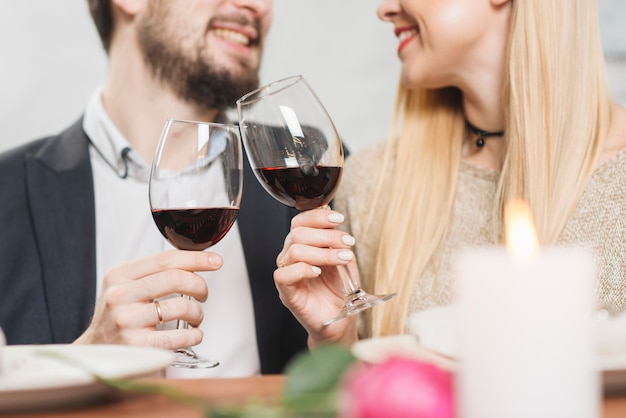 Crop laughing couple having wine