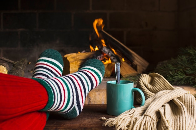 Crop legs and beverage near fireplace and scarf