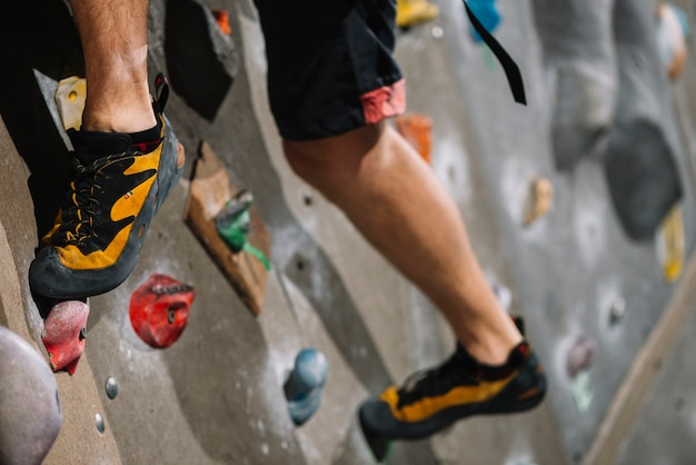 Crop legs on climbing wall