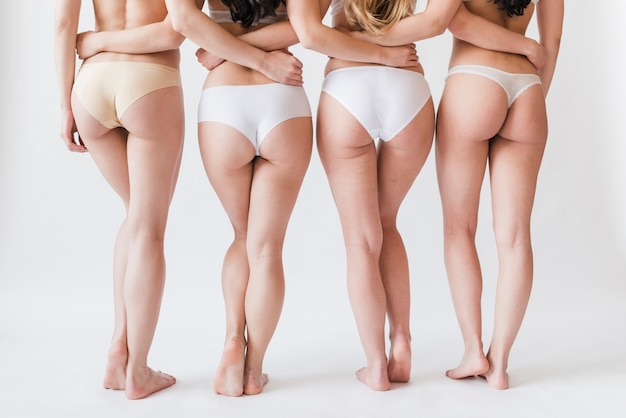 Crop legs of female group in underwear standing in row