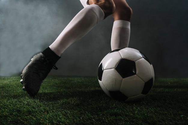 Crop legs kicking ball in smoke Free Photo