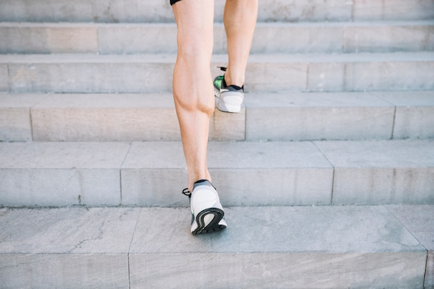 Crop legs leaping on cement stairs