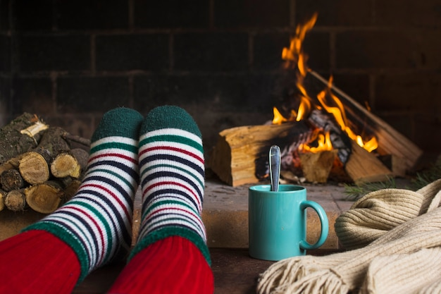 Crop legs near beverage and fireplace