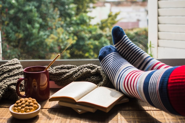 Crop legs near books and hot beverage
