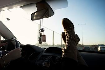 Crop legs near windscreen in car