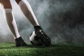 Crop legs shooting soccer ball