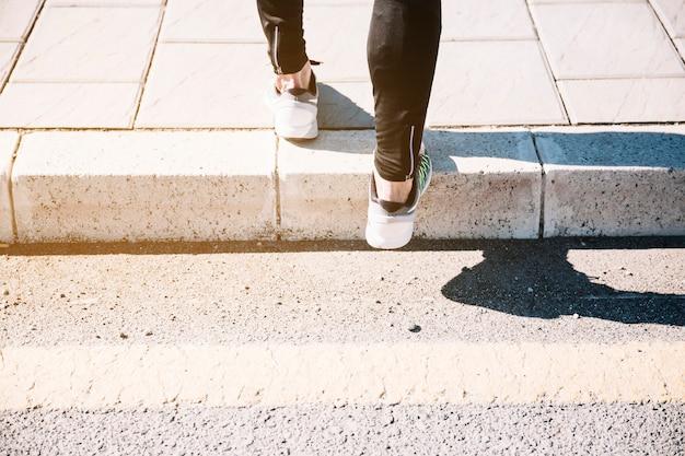 Ritaglia le gambe in scarpe da ginnastica sul marciapiede