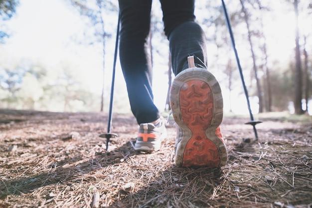 Crop legs walking in forest