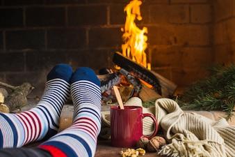 Crop legs warming near fireplace