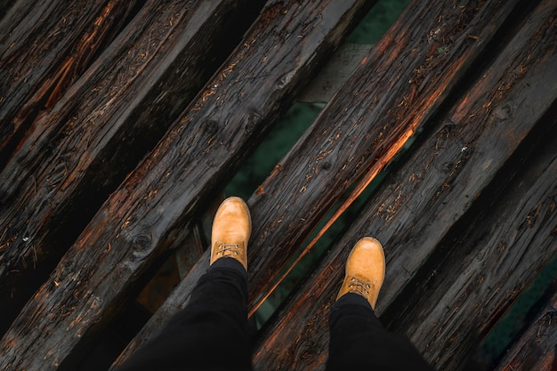Crop legs on wooden bridge