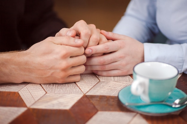 Crop loving couple holding hands at table