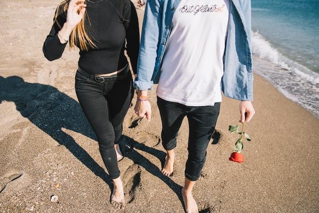 Crop loving people walking barefoot on beach