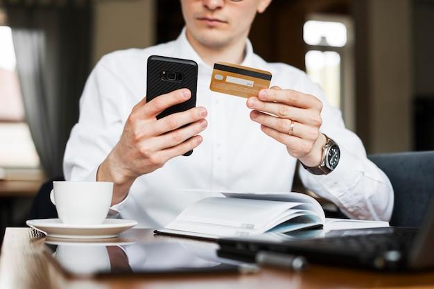 Обрезайте мужские руки, используя смартфон и золотую кредитную карту, сидя в кафе.