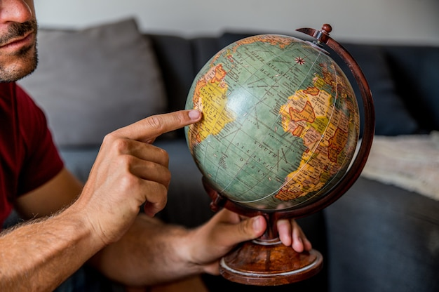 Crop male traveler with vintage globe at home