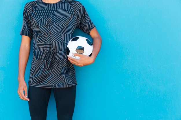 Crop male with football on blue backdrop