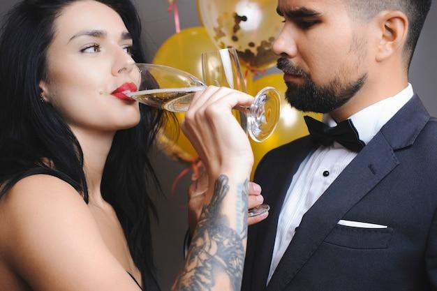 パーティーの風船の近くに立っている間、上質なシャンパンを楽しんでいるエレガントな衣装で男女をトリミングします