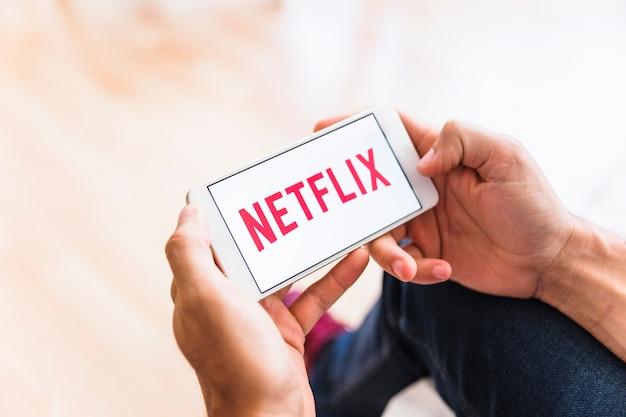 Crop man browsing smartphone with netflix logo