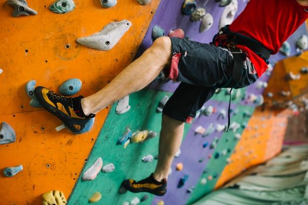 Crop man climbing wall