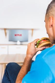 Crop man eating hamburger and watching Tv series