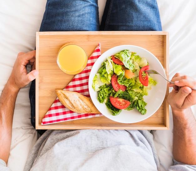 Crop man eating healthy food on bed
