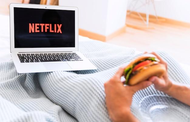 Crop man eating and watching netflix series