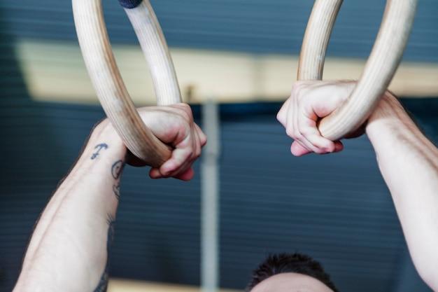Crop man exercising on gymnastic rings
