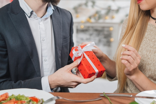Crop man giving small present to woman
