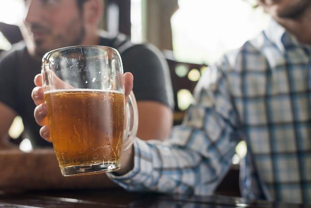 Crop man holding beer in bar