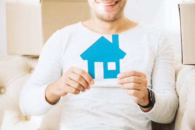 Crop man holding blue application of house