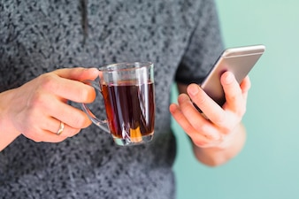 Crop man holding drink and smartphone