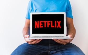 Crop man holding laptop with Netflix logo