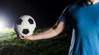 Crop man holding soccer ball