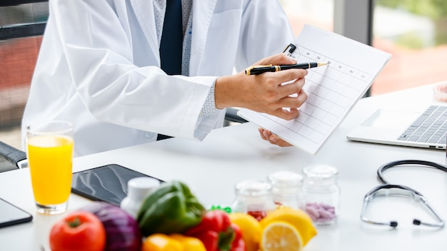 Человек в медицинской форме сидит за столом со здоровой пищей и витаминами и делает заметки в столе во время работы в больнице