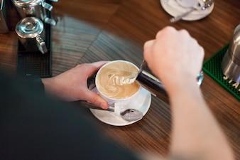 Crop man making tasty latte