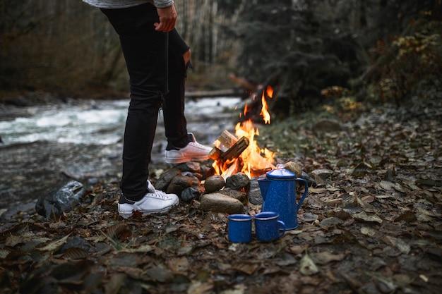 焚き火とカップの近くの作物男