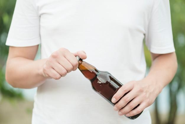 Crop man opening bottle of beer