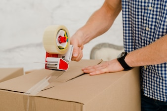 Crop man packing box with sticky tape