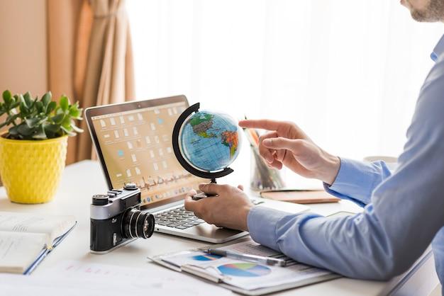 Человек урожая, указывая на земной шар в офисе