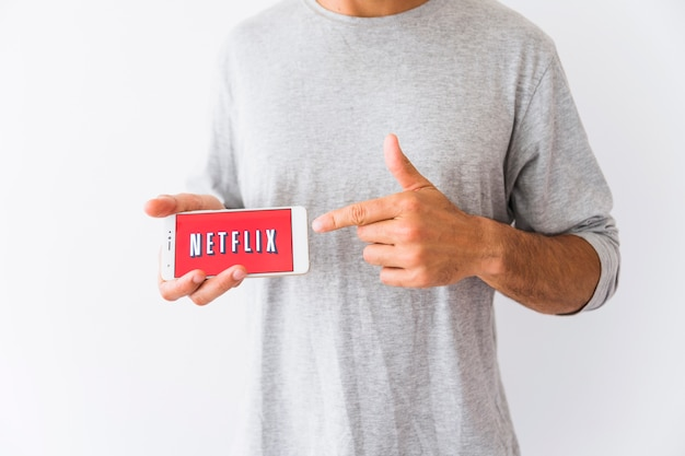 Crop man pointing at smartphone with netflix logo