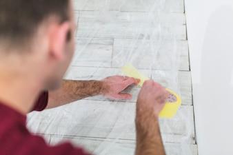 Crop man protecting floor with sheet