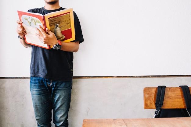 Raccolga il libro di lettura dell'uomo in aula