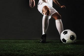Crop man running to kick ball