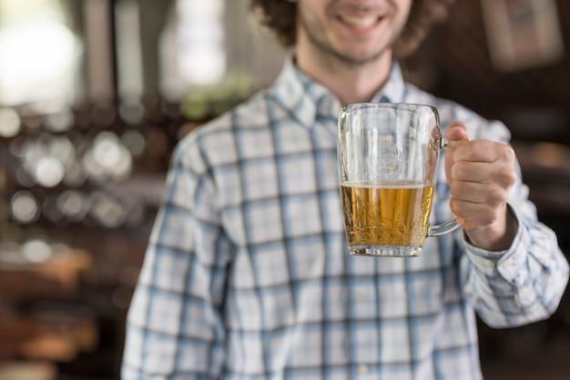 Crop man showing mug of beer in bar