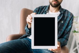 Crop man showing tablet