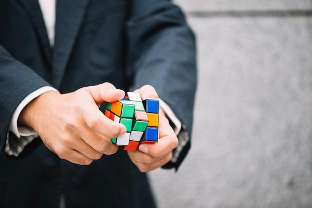 Crop man solving rubik's cube