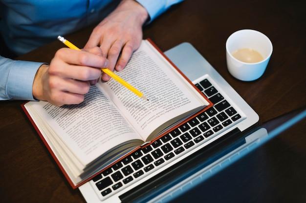 Crop man studying near laptop