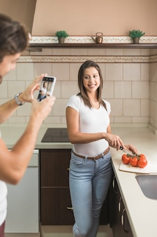 Crop man taking picture of cooking woman in kitchen