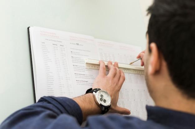Crop man underlining data in notebook