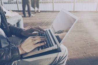 Crop man using laptop at street
