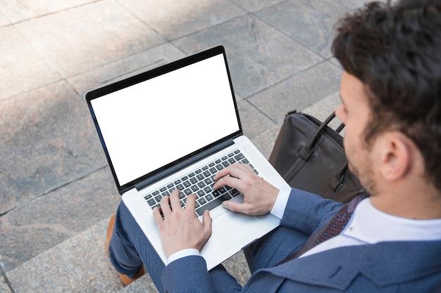 Crop man using laptop on stairs